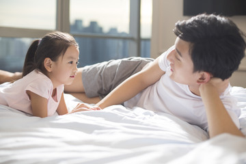 Cheerful young father playing with his daughter on bed