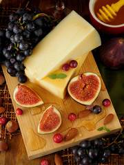 Parmesan on a board surrounded by figs and grapes. Ingredients for a cheese plate