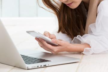 ノートパソコン・スマートフォンを操作する女性