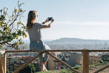 Rear view of young woman wearing in stripped t-shirt and jeans sitting on high point and photographing an urban landscape.Summer sunny day,rear view,view from a bird's eye view of city,city landscape.