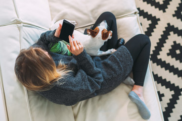 View from above. Young woman is sitting on white couch,using smartphone. There is dog nearby. Girl working, learning online, checking email. Distance work, online marketing, education. Social network.