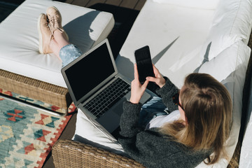 Sunny day. View from above. Young businesswoman is sitting on white couch on terrace, using laptop and smartphone. Girl working, blogging, learning online. Distance work. Online marketing, education.