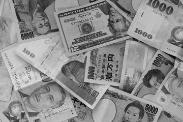Different International money banknotes bills stacked background with black and white color filter