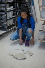 Girl looking at broken pieces of plate