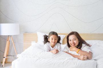 Happy asian family mother and daughter smiling on bed