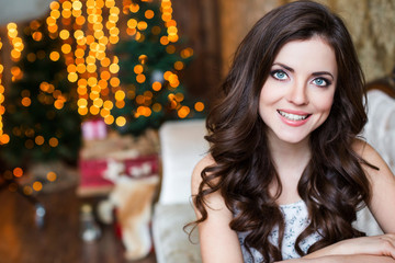Beautiful smiling woman on a blurred christmas background.
