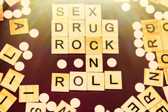 Wooden blocks on a pink background spelling words Sex Drug Rock n Roll surrounded by tablets. Art Style