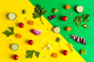 Eating pattern with raw ingredients of salad, lettuce leaves, cucumbers, red tomatoes, carrots, celery on colorful green and yellow background