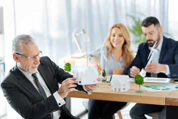 Tiny house. Excited professional engineer looking attentively at the model of a lovely house while his hardworking colleagues discussing the construction of a windmill turbine