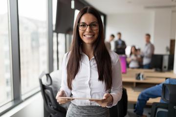 Portrait of successful businesswoman holding digital tablet