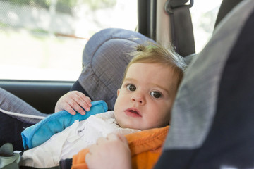 cute baby blonde girl, in car seat wearing seat belts happy is going to go in the path of the road. Spring or summer season