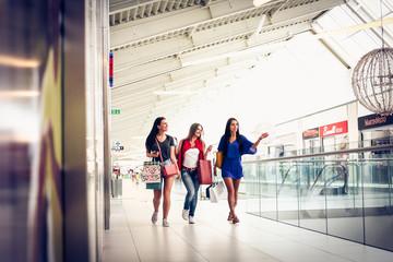 Young female friends walking trough shopping moll.