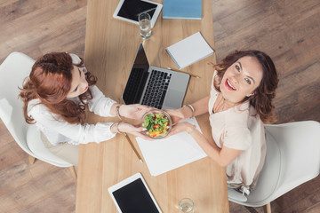 top view of coworkers holding bowl healthy salad at office