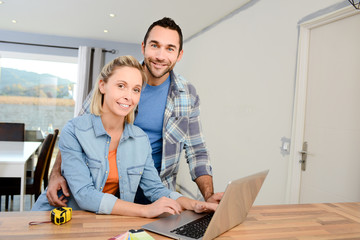 cheerful young couple renovating home design and choosing colors paint and furnitures on internet with a laptop computer