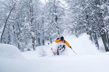 A male skier is riding in fresh powder snow at the Gosau valley in Austria.