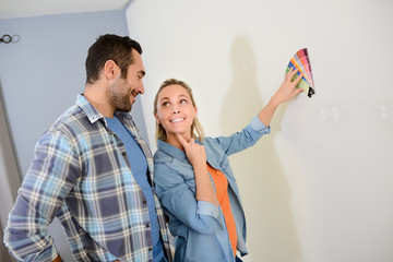 cheerful young couple choosing wall paint color for their new home decoration