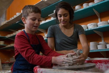 Female potter assisting boy in molding a clay