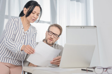 smiling middle aged businesswoman showing documents to man using laptop in office