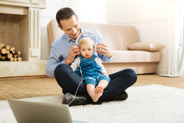 Pleasant sounds. Smart reliable attentive father feeling happy while putting big professional headphones on the head of his pretty baby and switching on very pleasant music