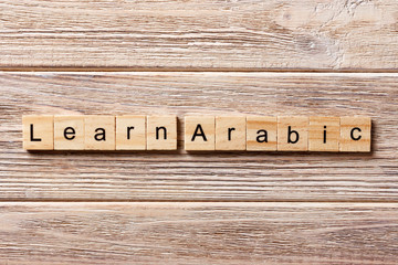 learn arabic word written on wood block. learn arabic text on table, concept