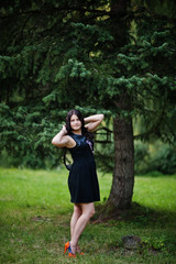Portrait of gorgeous girl wear on black at hen party, posed at park.