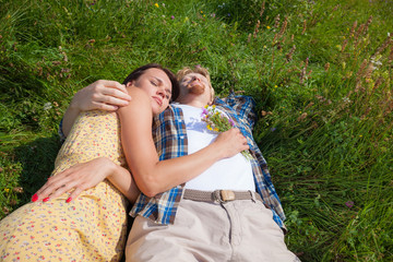 Young beautiful couple laying in the spring green meadow