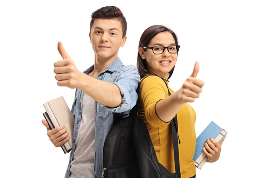Teenage students with backpacks and books making thumb up gestures