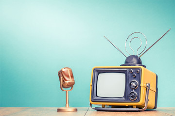 Retro old yellow TV receiver with antenna and golden microphone on wooden table front gradient aquamarine wall background. Vintage instagram style filtered photo