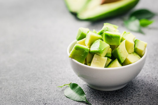 Fresh avocado slices in a bowl on concrete background. Selective focus, space for text.