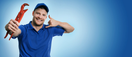 plumbing services - plumber with wrench showing phone call gesture on blue background with copy space