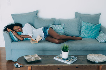 Beautiful black young woman sleeping in the sofa .
