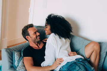 Happy young couple relaxed at home in the couch having fun playing with each other