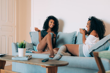 Happy young two black women sitting in the couch drinking coffee .