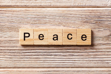 Peace word written on wood block. Peace text on table, concept