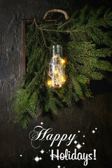 Christmas lights garland in glass bottle on green fir tree branches in wooden tray over dark texture background. Christmas holiday mood card. Top view with space