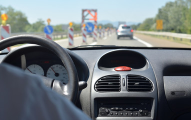 Driving a car on a highway with roadworks and with other vehicles blurred in front of him