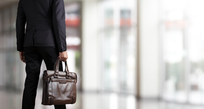 Businessman holding a briefcase in a modern office
