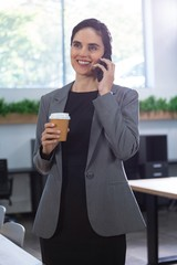 Female executive talking on mobile phone while having coffee