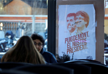 "A campaign poster of the political platform ""Junts per Catalunya"" showing ousted Catalan President Puigdemont and jailed former leader of the pro-independent movement Catalan National Assembly Jordi Sanchez, is seen ahead of regional elections in Barcelona"