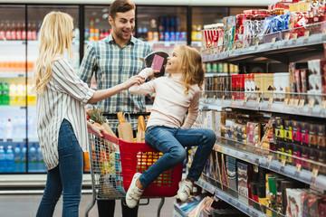 Joyful little girl sitting on a shopping cart