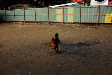 A Rohingya refugee baby carries a bag during a food supplies distribution by the World Food Programme at the Balukhali refugee camp near Cox's Bazar