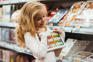 Smiling little girl choosing candy at the supermarket