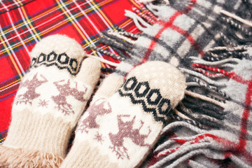 Woolen warm mittens and warm scarf on a red background. In anticipation of cold weather.