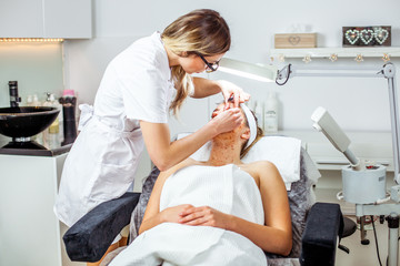 Cosmetologist woman is doing eyebrow modeling for woman / girl by Tweezers. Cosmetological clinic. Healthcare