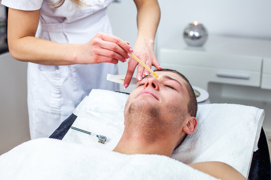 Cosmetologist woman is doing eyebrow modeling for man by wax for epilation. Cosmetological clinic. Healthcare