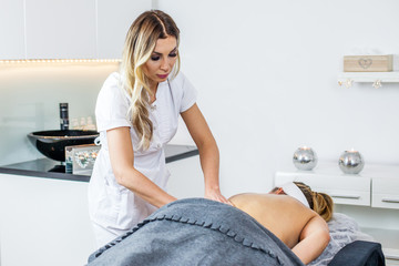 Cosmetologist/Therapist is doing body massage for young girl, woman.  Model. Cosmetological clinic. Healthcare