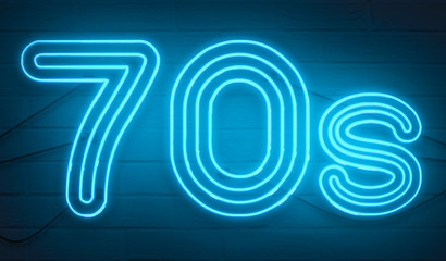 disco dance 70s neon sign lights logo text glowing color blue on dark black brick background, vintage style