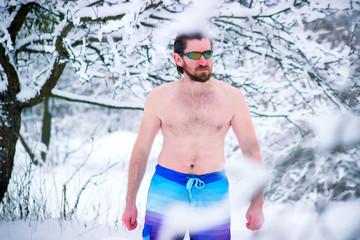Man enjoying snow bath outdoor after hot sauna