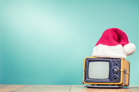 Retro TV in Santa hat front mint green background. Holidays congratulation in mass media concept. Vintage old style filtered photo