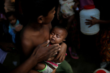 A boy holds a baby as Rohingya refugees wait to receive food supplies at a World Food Programme distribution at the Balukhali refugee camp near Cox's Bazar